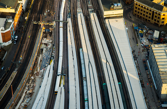 a subway travels through a fence