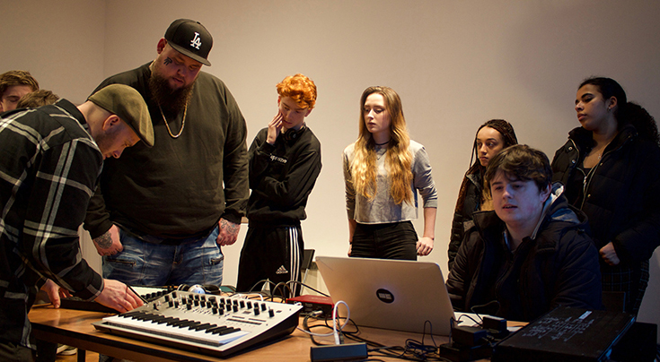 Group of people around a desk with sound recording equipment and a computer